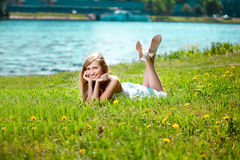 Beautiful smiling woman lying on the grass Stock Image