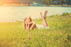 Beautiful smiling woman lying on the grass Royalty Free Stock Image