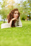 Beautiful smiling woman lying on a grass outdoor. Royalty Free Stock Image