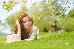 Beautiful smiling woman lying on a grass outdoor. Stock Photo
