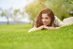 Beautiful smiling woman lying on a grass outdoor. Royalty Free Stock Photography