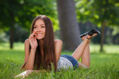 Beautiful smiling woman lying on a grass outdoor. Stock Photos