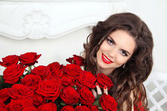Beautiful smiling woman with makeup, red roses bouquet of flower Royalty Free Stock Photography