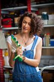 Smiling woman mechanic in blue denim overalls tries to hand prot. Beautiful smiling woman mechanic in blue denim overalls tries to hand protective gloves in the Stock Image
