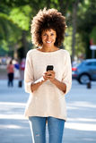 Beautiful smiling woman with mobile phone in park Stock Images