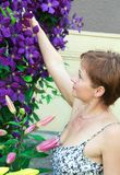 Beautiful smiling woman near the flowers Royalty Free Stock Image