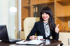 Beautiful smiling woman in office drinking coffee Royalty Free Stock Photography