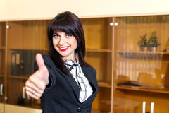 Beautiful smiling woman in office shows thumb up Royalty Free Stock Image