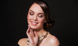 Beautiful smiling woman with perfect makeup wearing jewelry Stock Photos