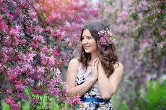 Beautiful smiling woman and pink flowers outside in spring Royalty Free Stock Photography