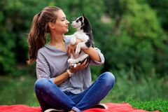 A beautiful smiling woman with a ponytail and wearing a striped shirt is playing with a sweet husky puppy while resting stock photos