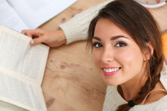 Beautiful smiling woman portrait lying on floor reading book Stock Image