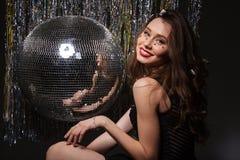 Beautiful smiling woman posing near disco ball Stock Images