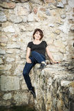 Beautiful smiling woman posing on the stone wall, beauty and fas Royalty Free Stock Image