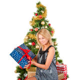 Beautiful smiling woman with the present near the Christmas tree Stock Photos