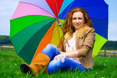 Beautiful smiling woman with a rainbow umbrella outdoors Stock Images