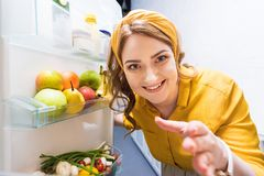 Beautiful smiling woman reaching hand in fridge. At kitchen stock images