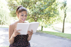 Beautiful smiling woman reading book in the park. Stock Image