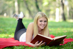 Beautiful smiling woman reading book in park stock photography