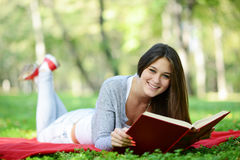 Beautiful smiling woman reading book in park Royalty Free Stock Image