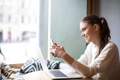 Beautiful smiling woman reading pleasant text message on mobile phone during work on laptop computer while sitting in modern coffe royalty free stock image
