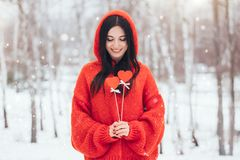 Beautiful smiling woman with red hearts for valentines day on winter background stock photos