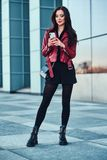 Beautiful smiling woman in red jacket is standing next to building and chating by mobile phone. Beautiful smiling woman in red jacket is standing next to glass royalty free stock photography