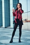 Beautiful smiling woman in red jacket is standing next to building and chating by mobile phone. Beautiful smiling woman in red jacket is standing next to glass royalty free stock photo