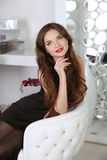 Beautiful smiling woman with red lips and long hair sitting in m Royalty Free Stock Photos