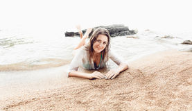 Beautiful smiling woman relaxing in sea waves on sandy beach Stock Image