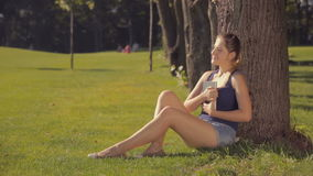 Beautiful smiling woman relaxing under the tree at park and holding a book. Smiling woman relaxing under the tree at park and holding a book stock video