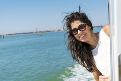 Beautiful smiling woman sailing on a boat with wind in the hair Royalty Free Stock Photo