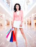 Beautiful smiling woman with shopping bags in mall Stock Photo