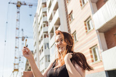 Beautiful smiling woman showing her new home keys against the backdrop of a house under construction Royalty Free Stock Photo