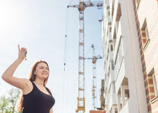 Beautiful smiling woman showing her new home keys against the backdrop of a house under construction Royalty Free Stock Image