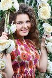 Beautiful smiling woman sits on swing. Overgrown with white roses Stock Image