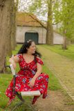 Beautiful smiling woman sitting on a bench in a red dress with blue flowers. Among green trees on a wonderful day in Limburg in the Netherlands, copy space or stock photography