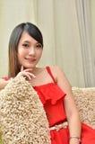 Beautiful smiling woman sitting on modern sofa Royalty Free Stock Photos