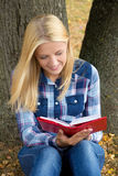 Beautiful smiling woman sitting in park and reading book Royalty Free Stock Images