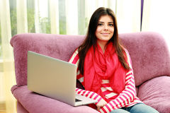 Beautiful smiling woman sitting on the sofa with laptop Royalty Free Stock Photos