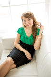Beautiful smiling woman sitting on white sofa and touching hair Stock Photography
