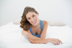 Beautiful smiling woman smiling cheerfully at camera while lying on her bed Stock Photos