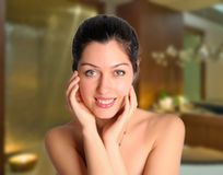 Beautiful smiling woman at spa salon. Pretty brunette woman cradles face at spa salon Royalty Free Stock Photos