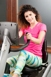 Beautiful smiling woman spinning the stationary bicycle Royalty Free Stock Images