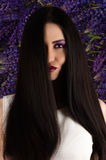 Beautiful smiling woman with straight hair on background of Lupine flowers Royalty Free Stock Images