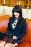 Beautiful smiling woman in a suit sitting in  office on the co Stock Images