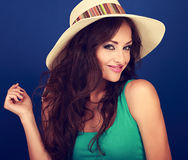 Beautiful smiling woman in summer hat with curly long brown hair. With manicured nails posing on blue background Stock Image