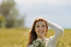 Beautiful smiling woman in sunny autumn field with bunch of camo. Miles looking up Stock Photo