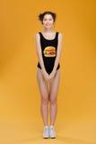 Beautiful smiling woman in swimsut with hamburger print standing straight Stock Photo