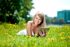 Beautiful smiling woman with tablet pc, outdoors. Beautiful youn Stock Photography